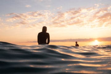 Photograph of Byron Bay surfers sitting on surfboard at sunset waiting for a wave